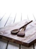 2 деревянных варя ложки на голубом полотенце на деревянном столе Стоковые Изображения