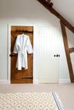 2 деревянных двери и купальный халат в просторной квартире Стоковые Фото