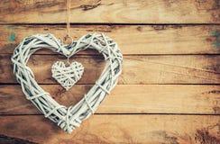 2 деревянных деревенских декоративных сердца вися на винтажном деревянном ба Стоковые Изображения