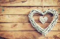2 деревянных деревенских декоративных сердца вися на винтажном деревянном ба Стоковое фото RF