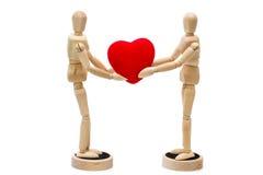 2 деревянных куклы, манекены держа красное сердце над задней частью белизны Стоковое Изображение RF