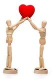 2 деревянных манекена кукол держа красное сердце Стоковое Изображение RF