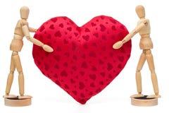 2 деревянных манекена кукол держа огромное красное сердце над белизной Стоковое Изображение RF