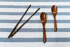 2 деревянных ложки и китайских палочки на белом Striped Backgr Стоковые Изображения RF