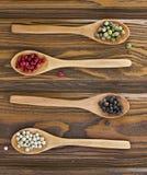 4 деревянных ложки с перцами цвета Стоковые Изображения