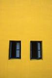2 деревянных окна на желтом фасаде Стоковое Изображение