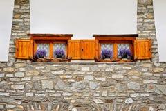 2 деревянных окна с фиолетовыми цветками на высокогорной архитектуре Стоковые Фото