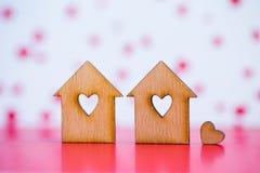 2 деревянных дома с отверстием в форме сердца с меньшим сердцем o Стоковое Изображение