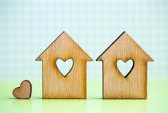 2 деревянных дома с отверстием в форме сердца с меньшим сердцем o Стоковое Фото
