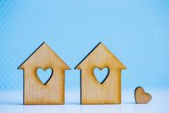2 деревянных дома с отверстием в форме сердца с меньшим сердцем o Стоковые Изображения