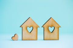 2 деревянных дома с отверстием в форме сердца с меньшим сердцем o Стоковые Фото