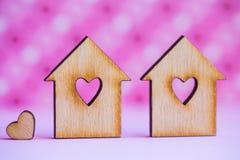 2 деревянных дома с отверстием в форме сердца с меньшим сердцем o Стоковые Изображения RF