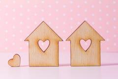 2 деревянных дома с отверстием в форме сердца с меньшим hea Стоковые Фотографии RF
