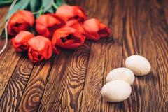 3 деревянных пасхального яйца и красных тюльпаны на деревянной предпосылке Стоковые Изображения