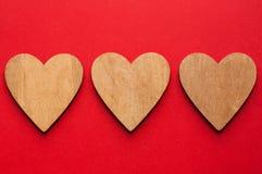3 деревянных сердца Брайна на красной бумажной предпосылке Стоковые Изображения