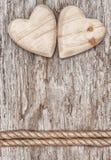 2 деревянных сердца и веревочки на старой древесине Стоковые Изображения