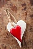2 деревянных сердца, красный цвет и белизны на старой древесине Стоковое Изображение RF