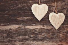 2 деревянных сердца на деревянной предпосылке Скопируйте космос, мягкий фокус, тонизированный, винтажный стиль Стоковые Изображения
