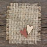2 деревянных сердца на холсте на деревянной предпосылке Стоковые Фотографии RF