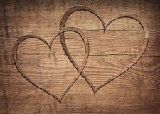 2 деревянных сердца помещенного на бурой древесной доске Стоковая Фотография