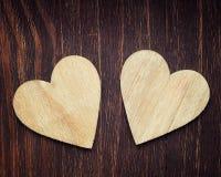 2 деревянных сердца помещенного славно на деревянном backrgound Стоковое Фото
