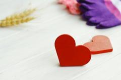 2 деревянных сердца с носками, перчатками на деревянном ба Стоковые Фото