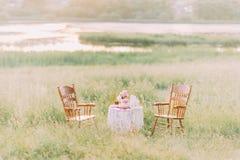 2 деревянных стуль и винтажной таблица украшенные с бутылками, свечами, тканью, вереском стоя в саде Стоковое фото RF