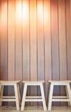 3 деревянных стуль на предпосылке стены Стоковые Изображения