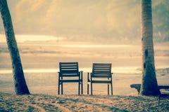 2 деревянных стуль на тропическом пляже во время захода солнца - Луна и Стоковые Изображения