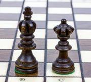 2 деревянных части шахмат самостоятельно на доске шахмат Стоковые Изображения