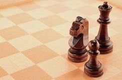 3 деревянных шахматной фигуры на доске Стоковые Изображения