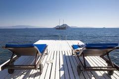 2 деревянных шезлонга на белой пристани морем против b Стоковое фото RF