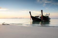 2 деревянных шлюпки на пляже на времени восхода солнца Стоковая Фотография