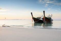 2 деревянных шлюпки на пляже на времени восхода солнца Стоковые Изображения