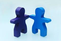 2 деревянных люд игрушки рука об руку Стоковое Изображение