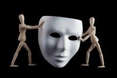 2 деревянных figurines держа белую маску человеческого лица изолированный дальше Стоковая Фотография RF