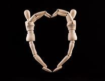 2 деревянных figurines формируя сердце формируют - влюбленность и отношение Стоковая Фотография