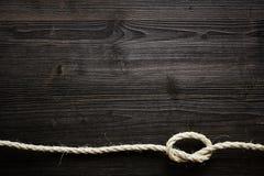 Естественная веревочка с узлом на темной древесине Стоковое фото RF