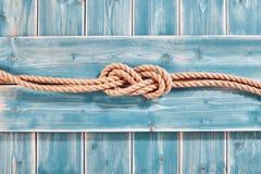 Естественная двузначная цифра веревочки 8 узлов на голубой древесине Стоковые Изображения RF