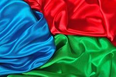 Естественная голубая, красная и зеленая текстура ткани сатинировки Стоковое Фото