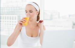 Естественная милая спортсменка наслаждаясь апельсиновым соком Стоковые Фотографии RF