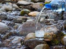 Естественная питьевая вода льется в стекло стоковое изображение