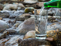 Естественная питьевая вода льется в стекло стоковое изображение rf