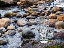 Естественная питьевая вода льется в стекло стоковые изображения rf