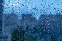 Естественная предпосылка падения воды на стекле Запачканная предпосылка города стоковое изображение