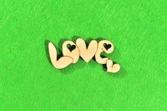 """Естественное деревянное слово """"любовь """"на зеленой предпосылке как трава стоковое изображение"""