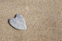Естественно камень сердца форменный на песке Стоковые Фото