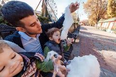 Естественные изображения счастливой семьи из четырех человек имея outsiade потехи и есть зубочистку сахара семья 4 стоковое фото