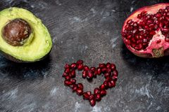 Естественные противостарители - гранатовое дерево уговаривать, красные семена аранжировало в форме сердца, плода авокадоа лежит р стоковое фото