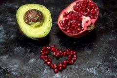 Естественные противостарители - гранатовое дерево уговаривать, красные семена аранжировало в форме сердца, плода авокадоа лежит р стоковое фото rf